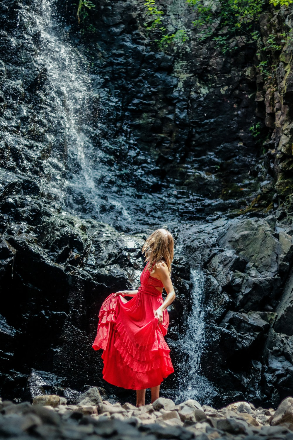 woman in red dress standing on rocky river