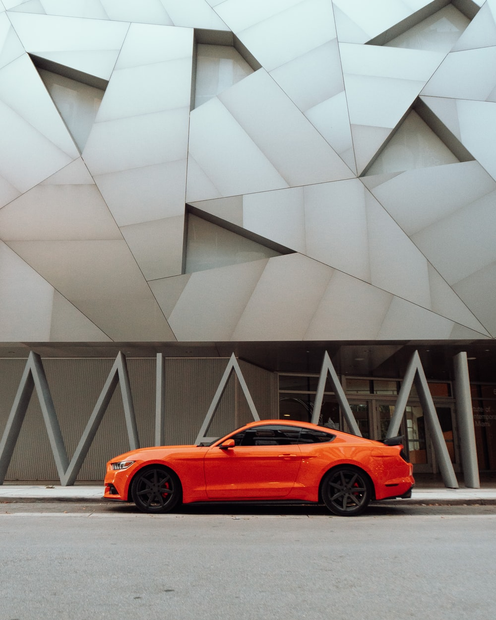 orange coupe parked near gray concrete building