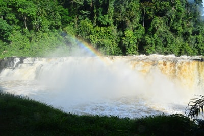 water falls near green trees during daytime gabon teams background