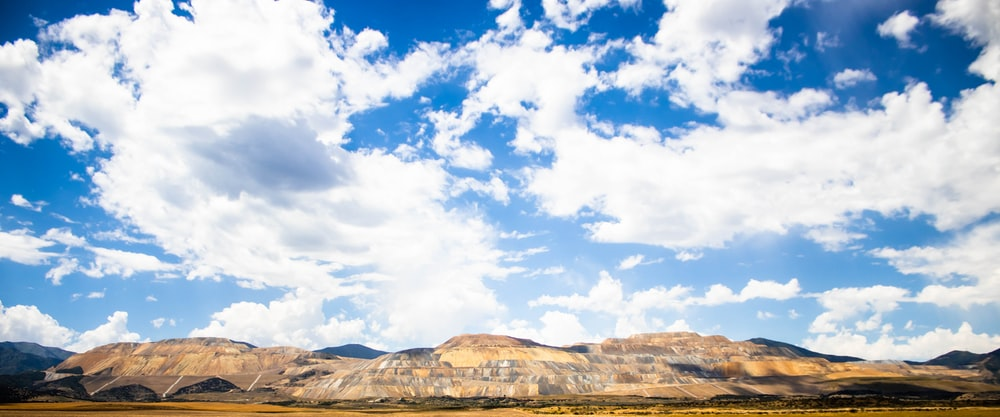brown and white mountains under blue sky and white clouds during daytime