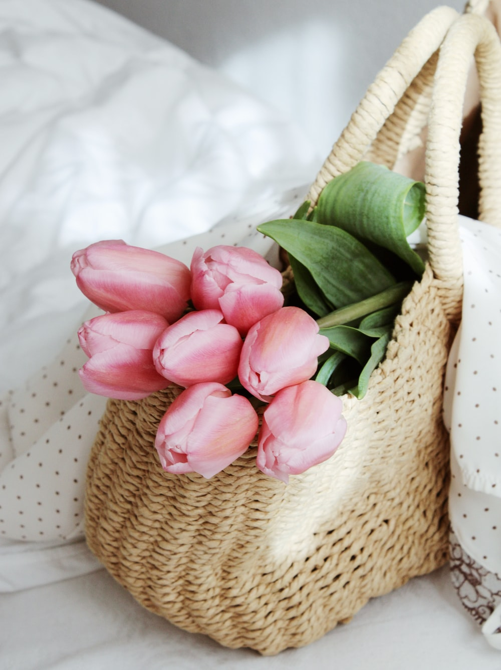 pink tulips on brown woven basket