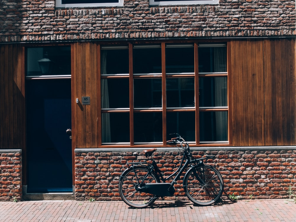 black bicycle parked beside brown wooden door