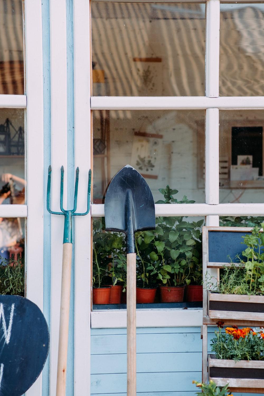 green and black shovel on white wooden framed glass window