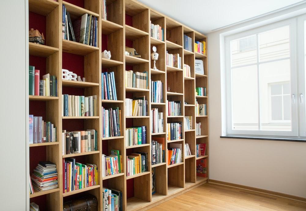 brown wooden book shelves near window