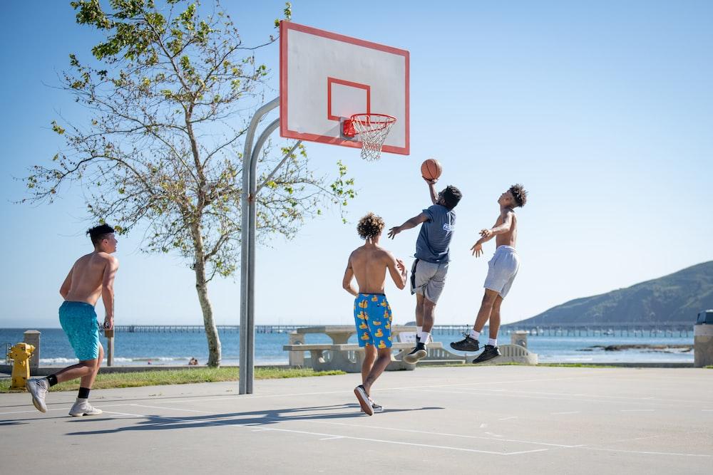 2 women playing basketball during daytime