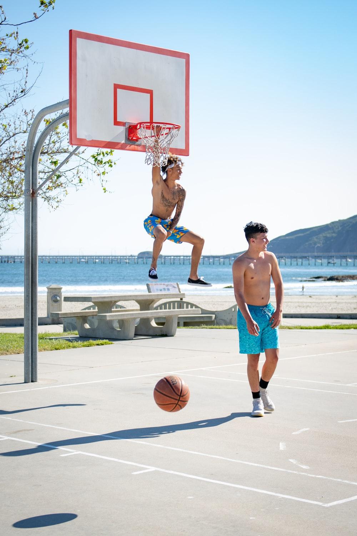 2 men playing basketball on basketball court during daytime
