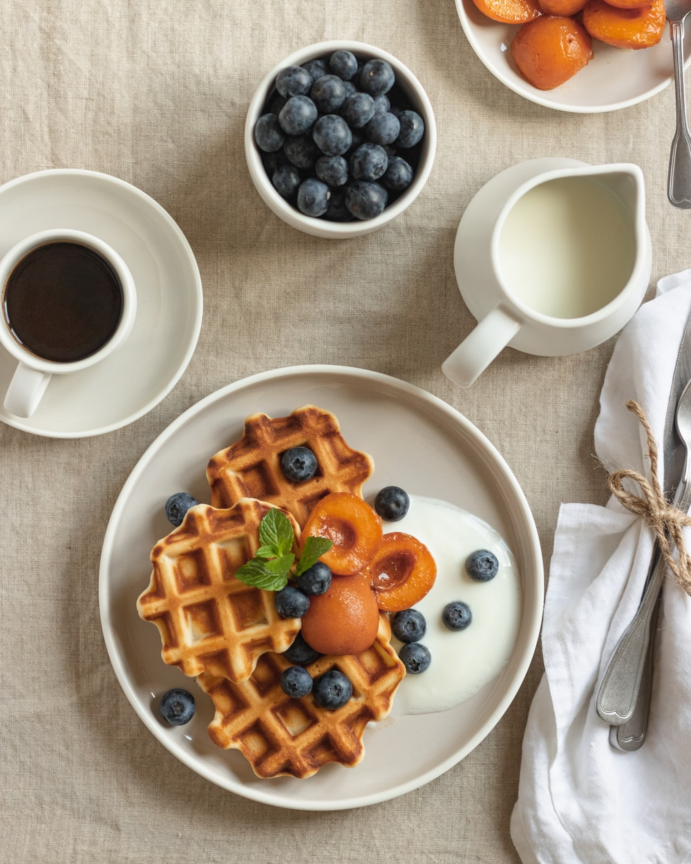 waffle with sliced strawberries and blueberries on white ceramic plate