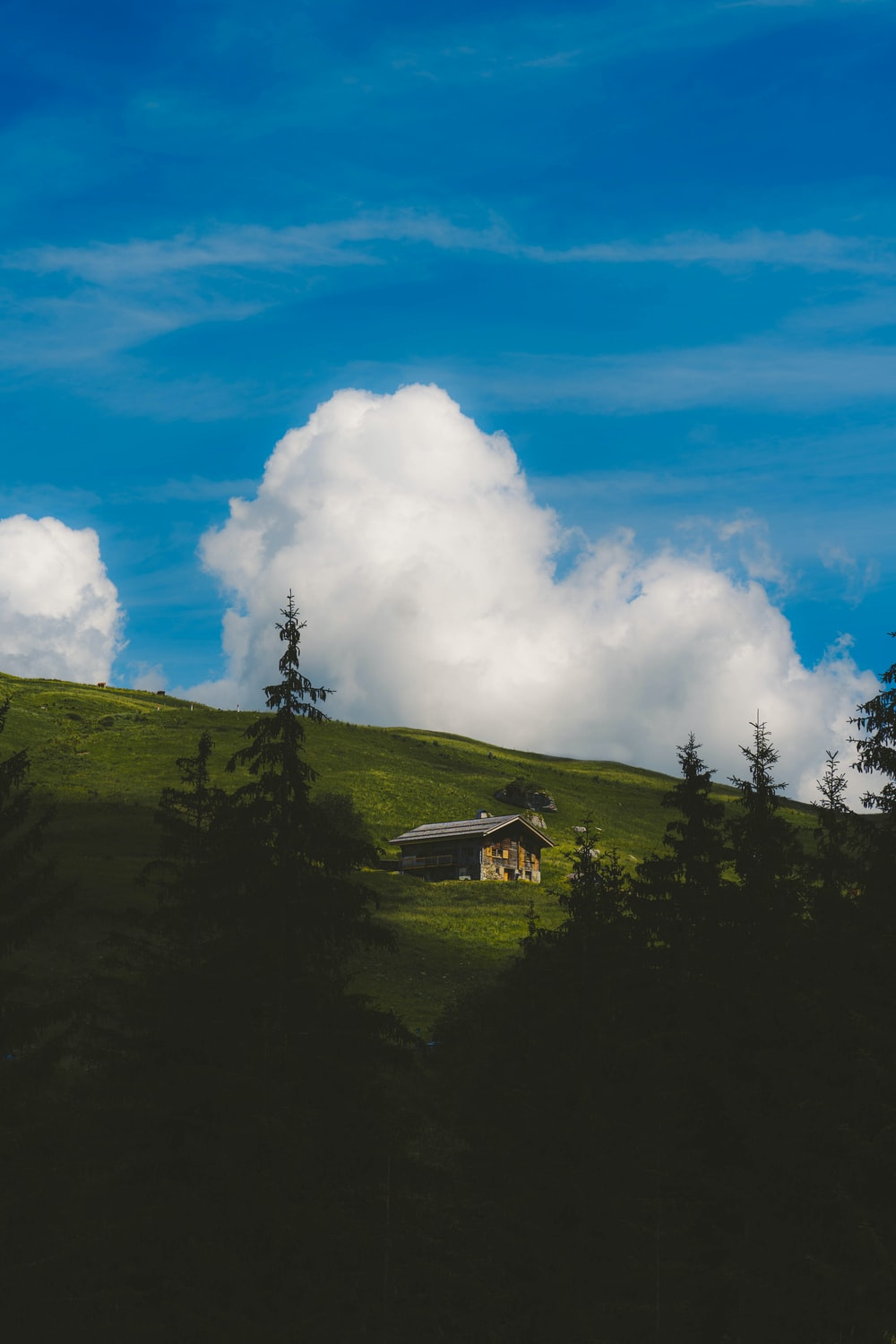 green mountain under blue sky and white clouds during daytime