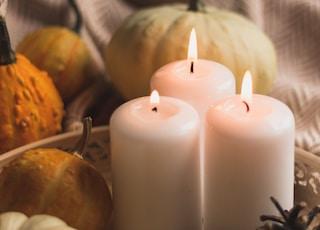 white pillar candle beside orange pumpkin and white pumpkin