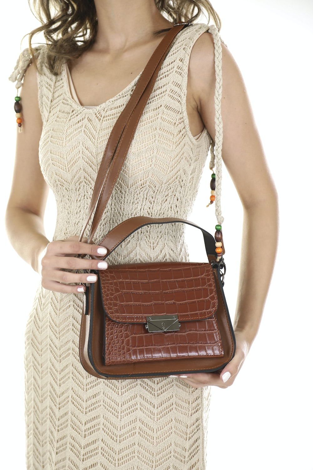 woman in white lace tank top carrying brown leather sling bag