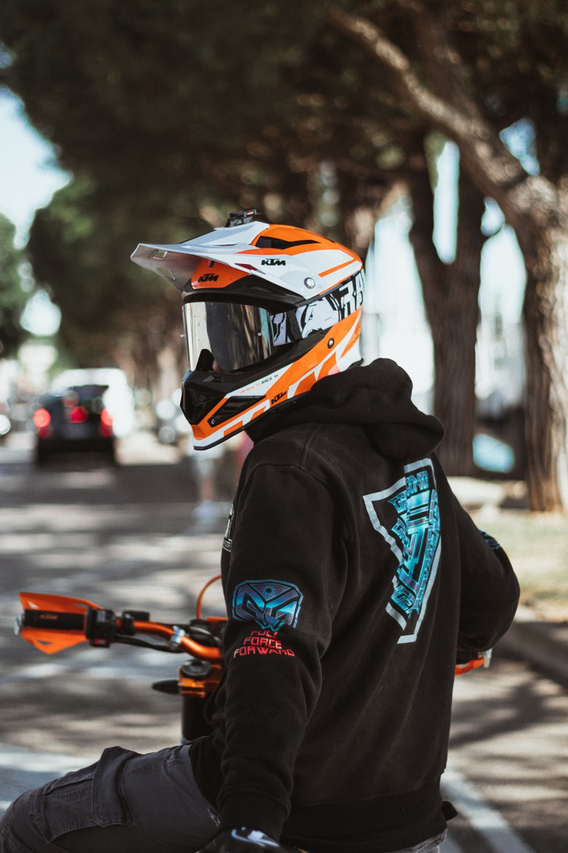 person in black and orange helmet and black hoodie holding orange and black nerf gun