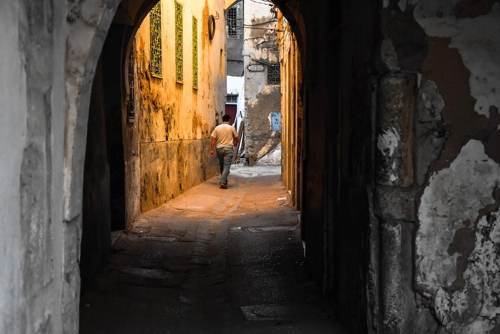 man in white shirt walking on hallway