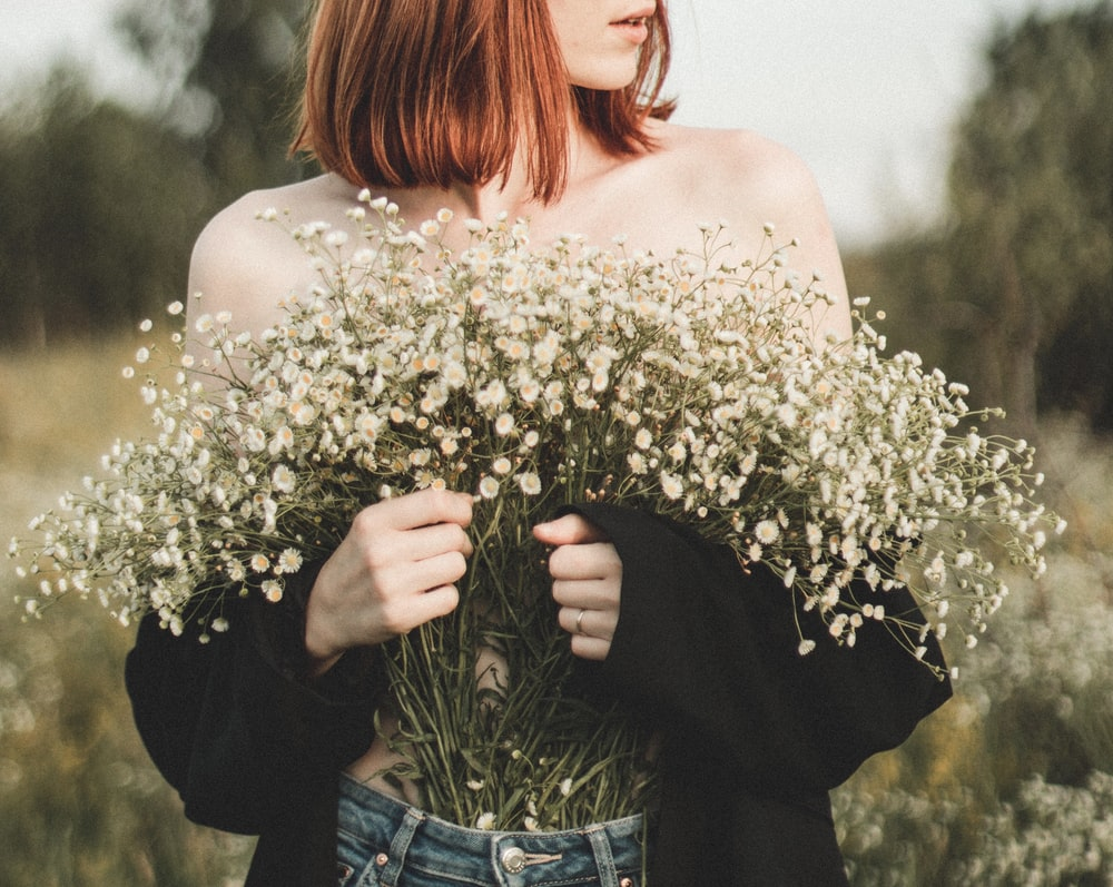 woman in white floral off shoulder shirt and blue denim jeans holding white flowers