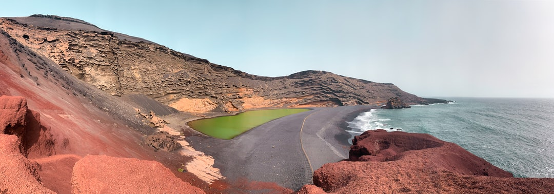 Volcanic scenery with a green lake and the ocean view in Lanzarote, Spain