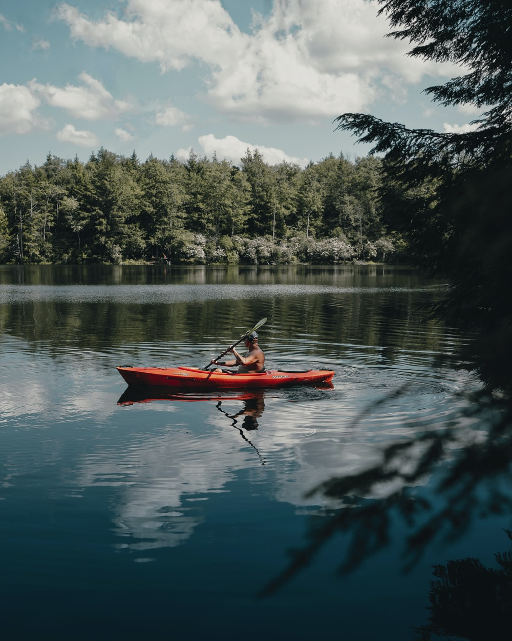 person riding red kayak on lake during daytime