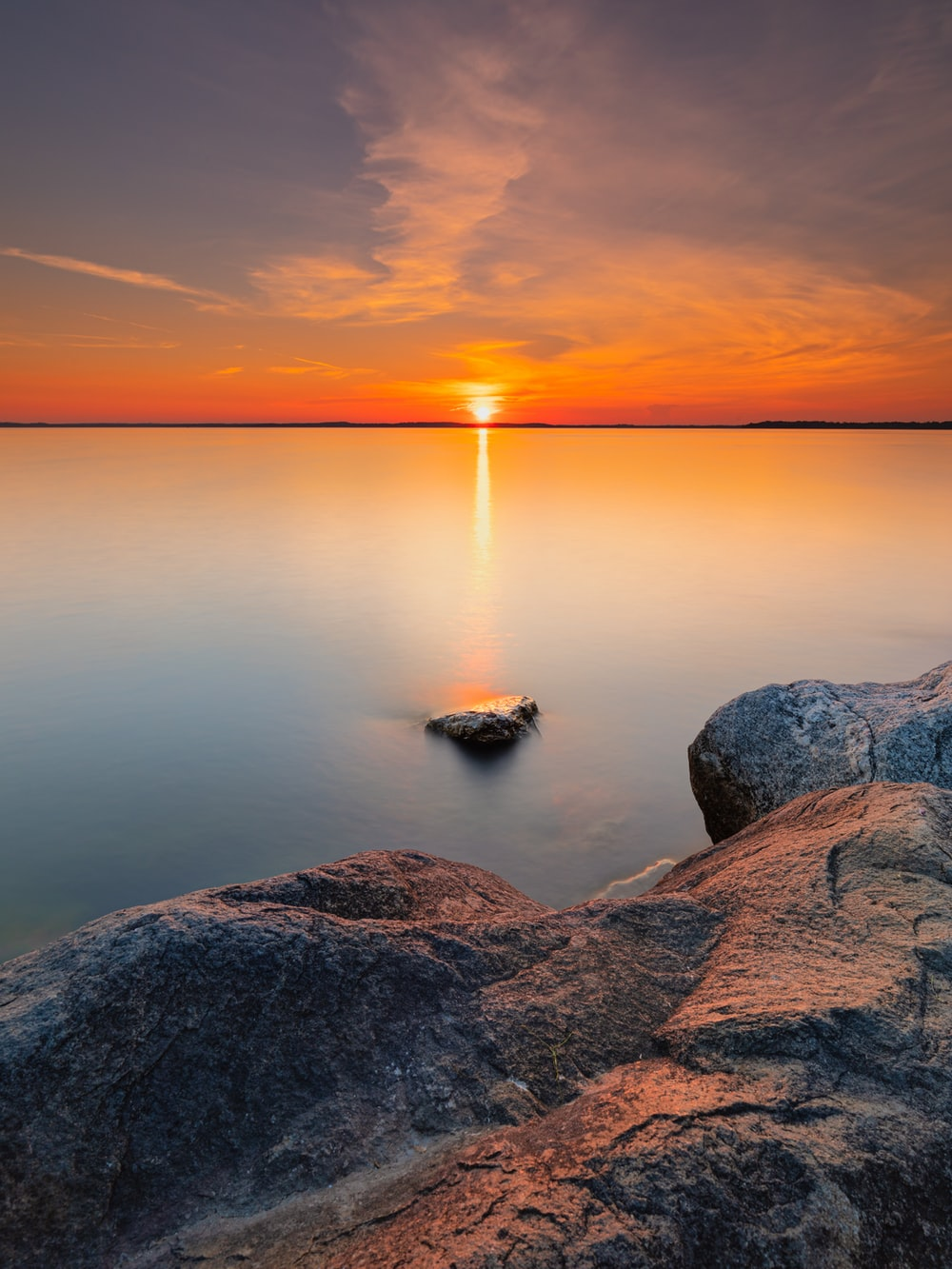 gray rock formation near body of water during sunset