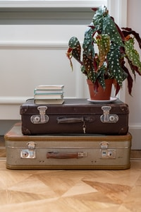 brown leather suitcase on brown wooden table