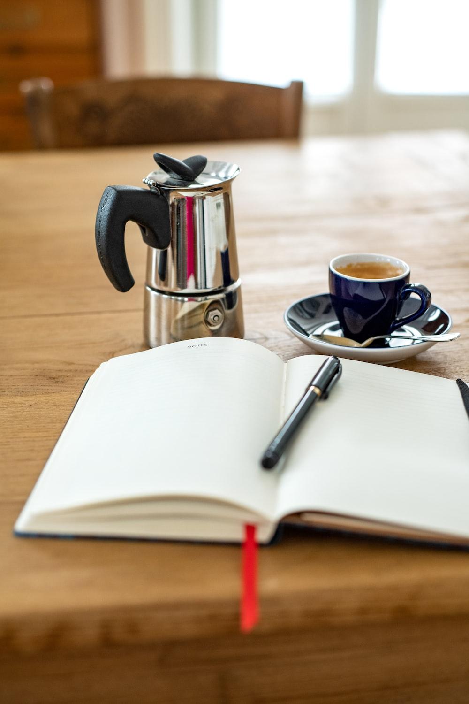 white and blue ceramic mug on white ceramic saucer beside silver and black teapot