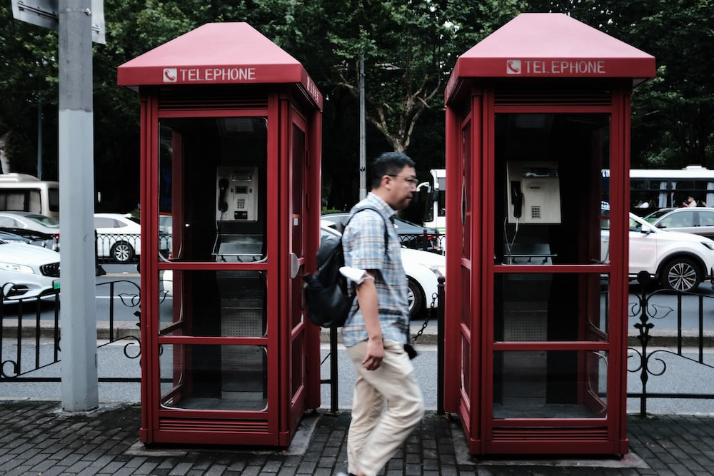 man in blue denim shorts standing beside red telephone booth