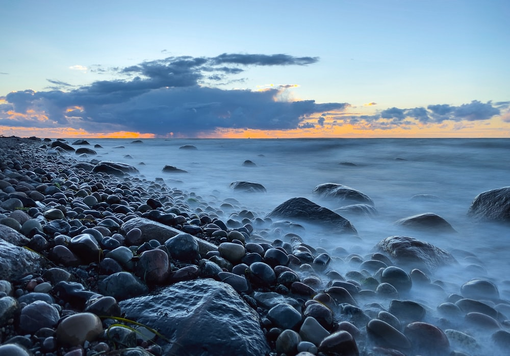 rocky shore with water waves during sunset