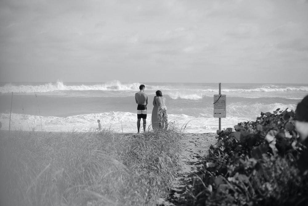 grayscale photo of couple walking on beach