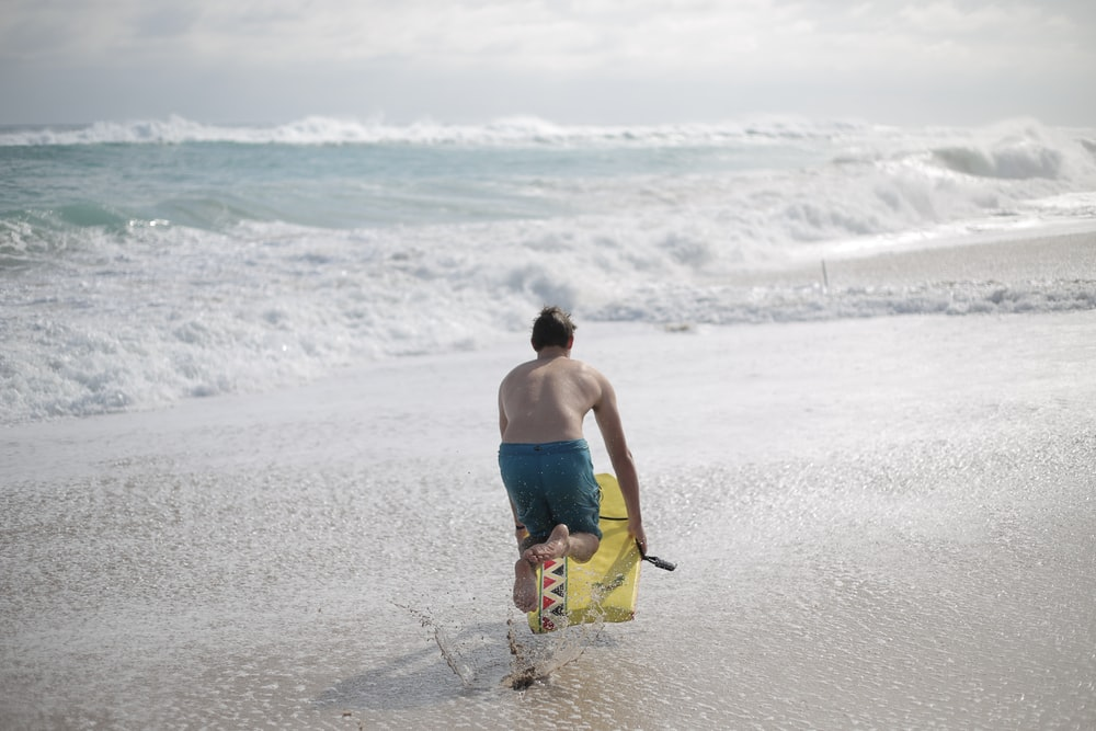 man in blue and yellow board shorts walking on beach during daytime