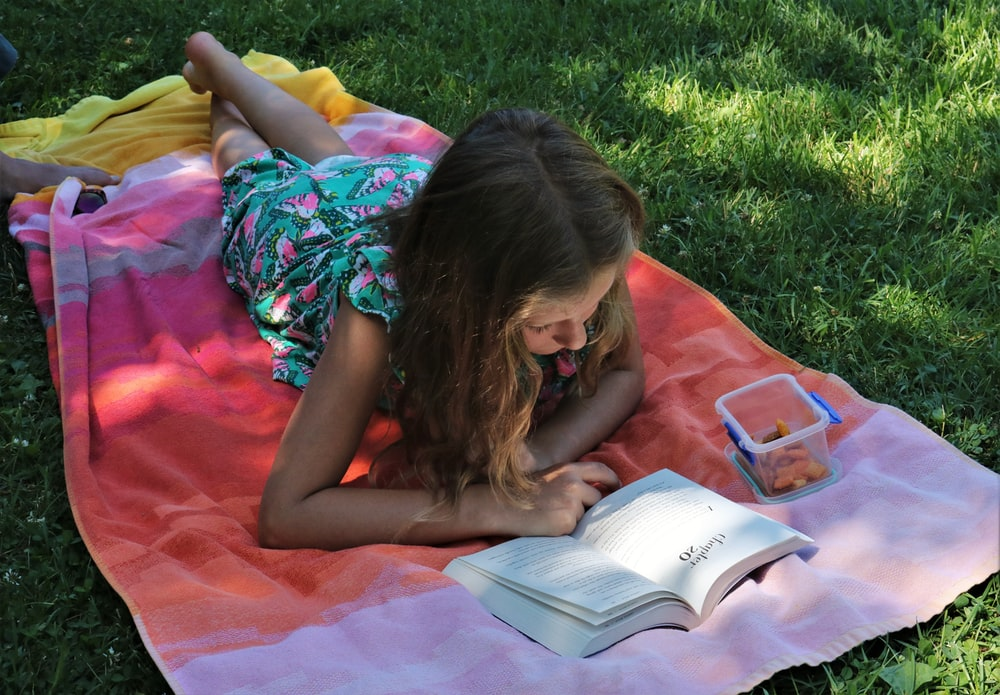 girl in pink dress reading book on green grass during daytime
