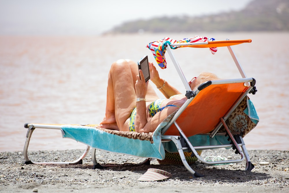 woman in white bikini lying on blue and white surfboard on beach during daytime