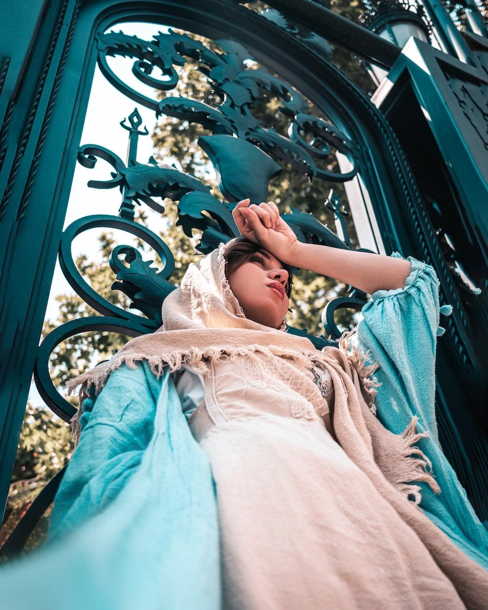 girl in white dress lying on blue hammock
