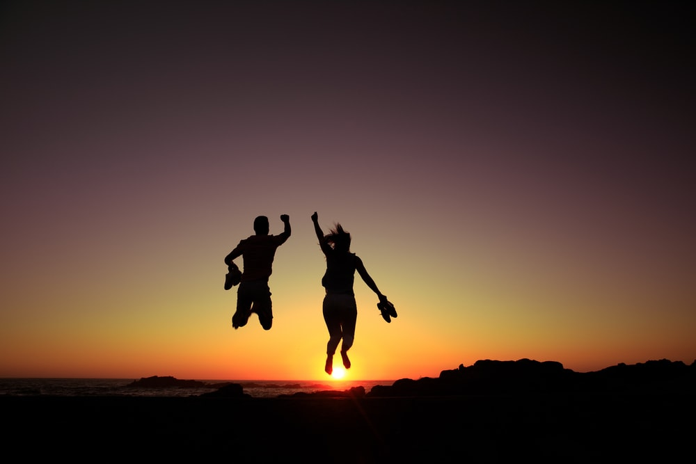 silhouette of 2 person jumping during sunset