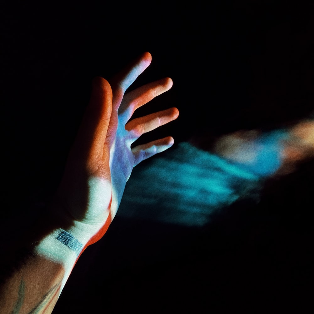 persons left hand with blue and purple light
