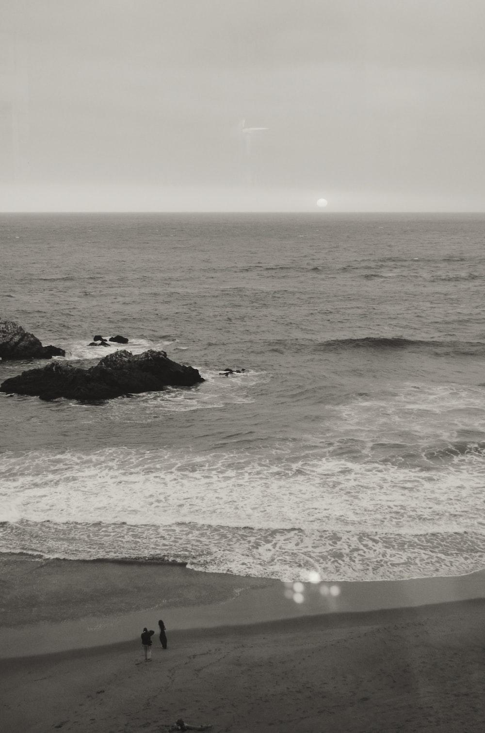 grayscale photo of ocean waves crashing on rocks