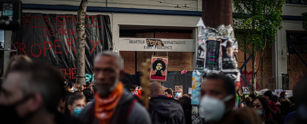man in black and orange jacket standing near people during daytime