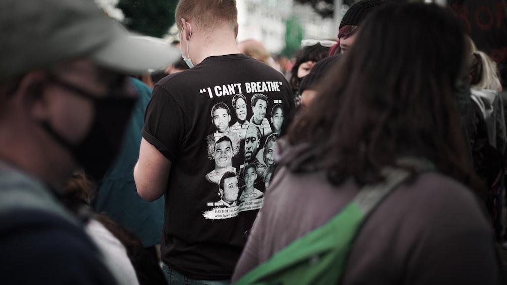 man in black crew neck t-shirt standing beside man in green jacket