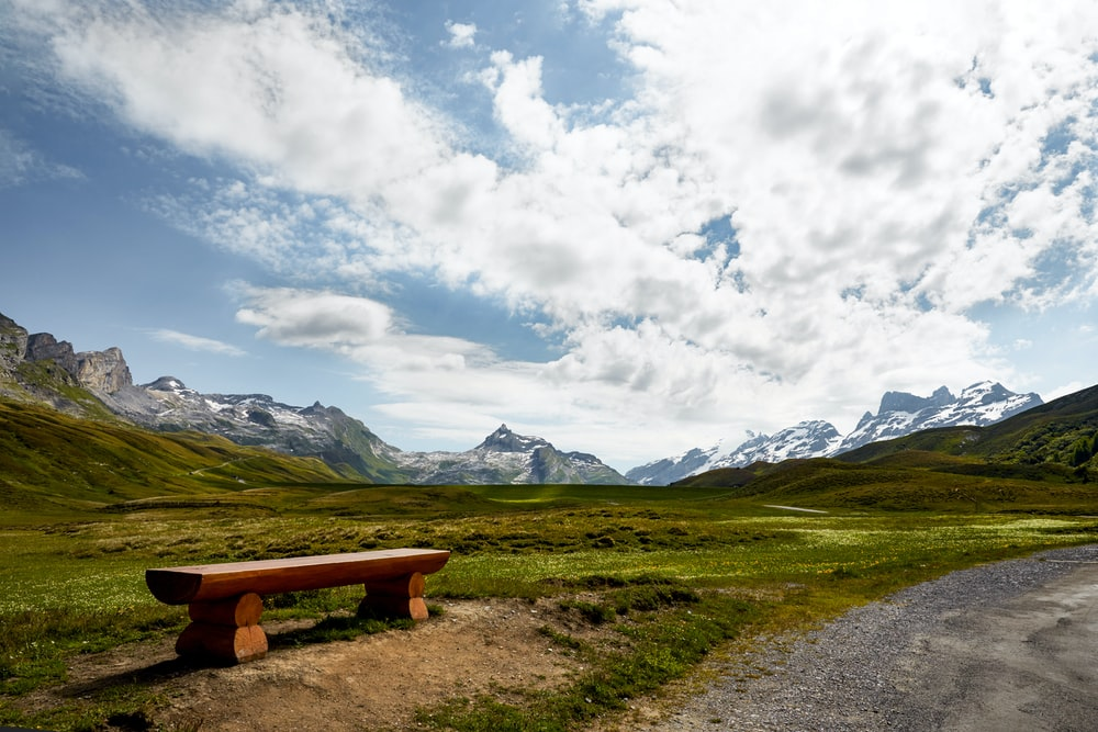 brown wooden bench on green grass field near mountain under white clouds during daytime