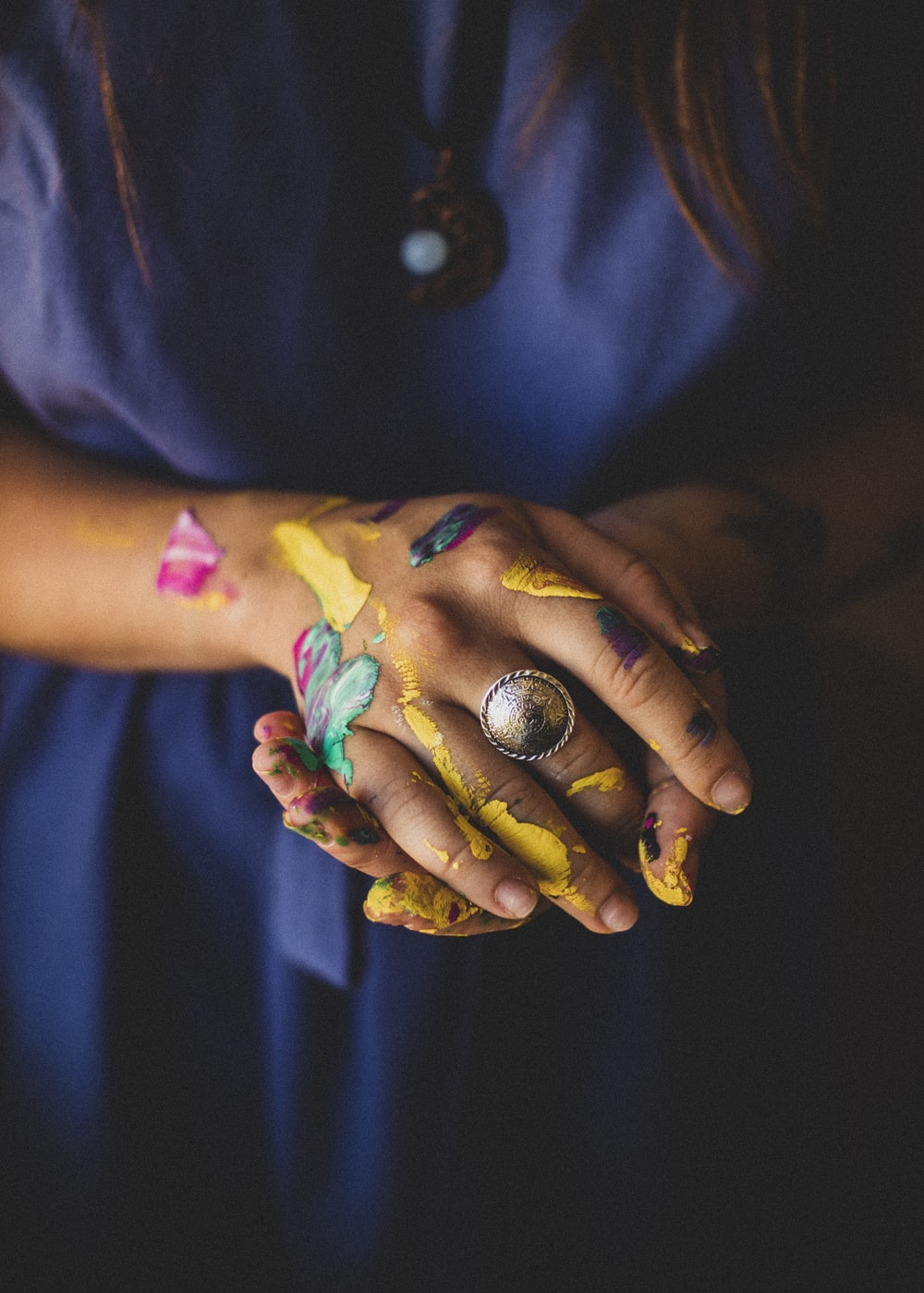 person with purple blue and green paint on hand