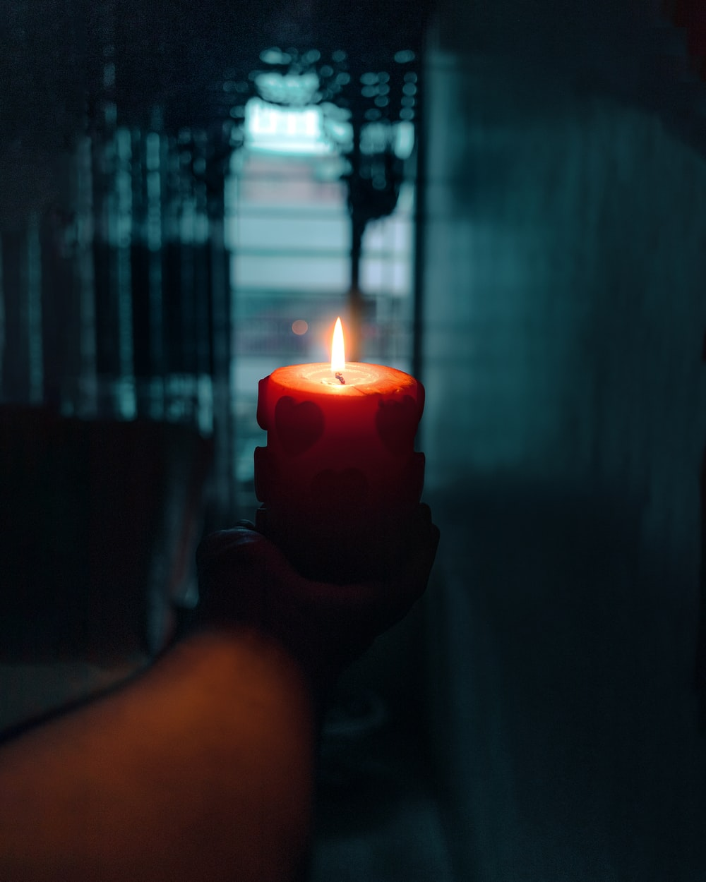 person holding red pillar candle