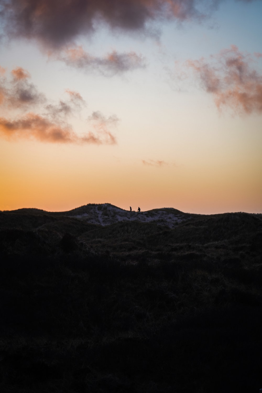silhouette of person standing on top of mountain during sunset