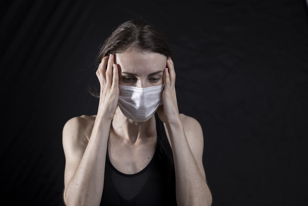 woman in black tank top covering her face with her hands
