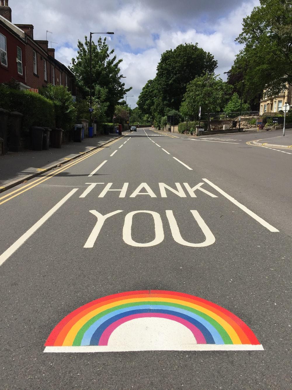 black asphalt road with rainbow sign