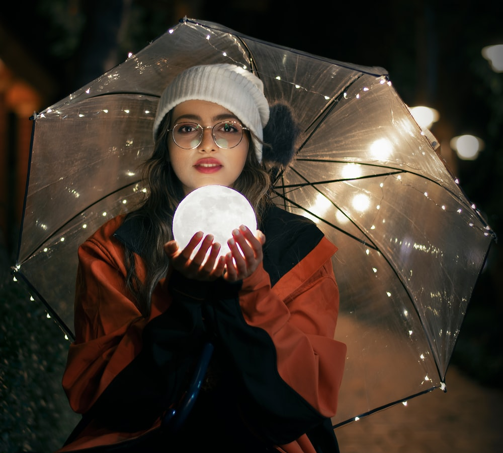 woman in red and black jacket holding umbrella