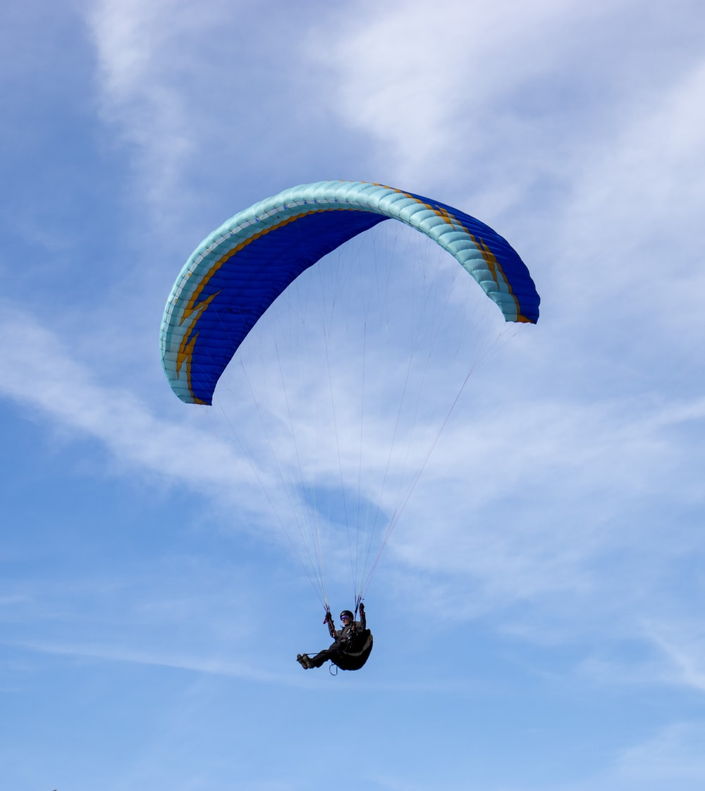 person riding on yellow and blue parachute under blue sky during daytime