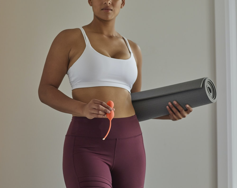 woman in white sports bra and purple leggings holding black speaker