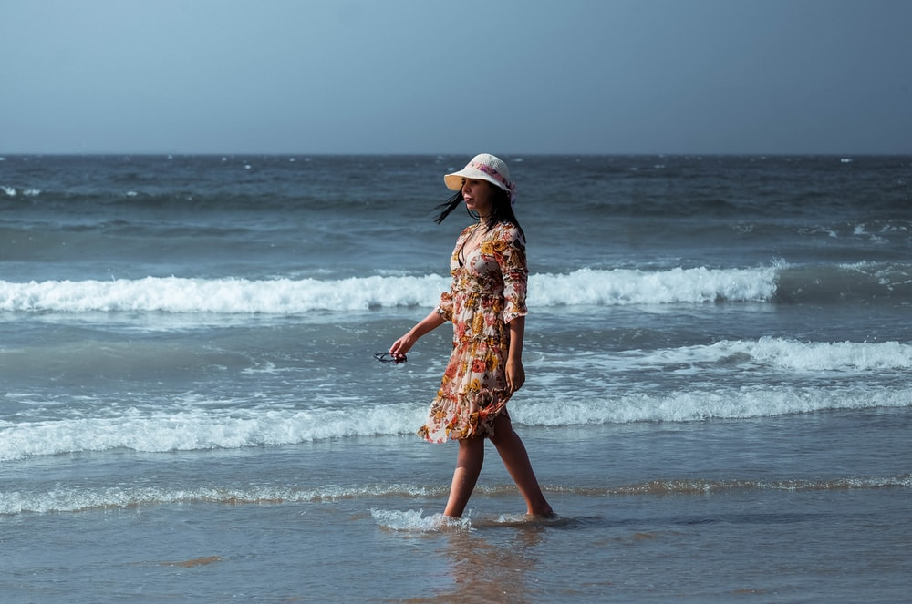woman in brown and white floral dress standing on beach during daytime