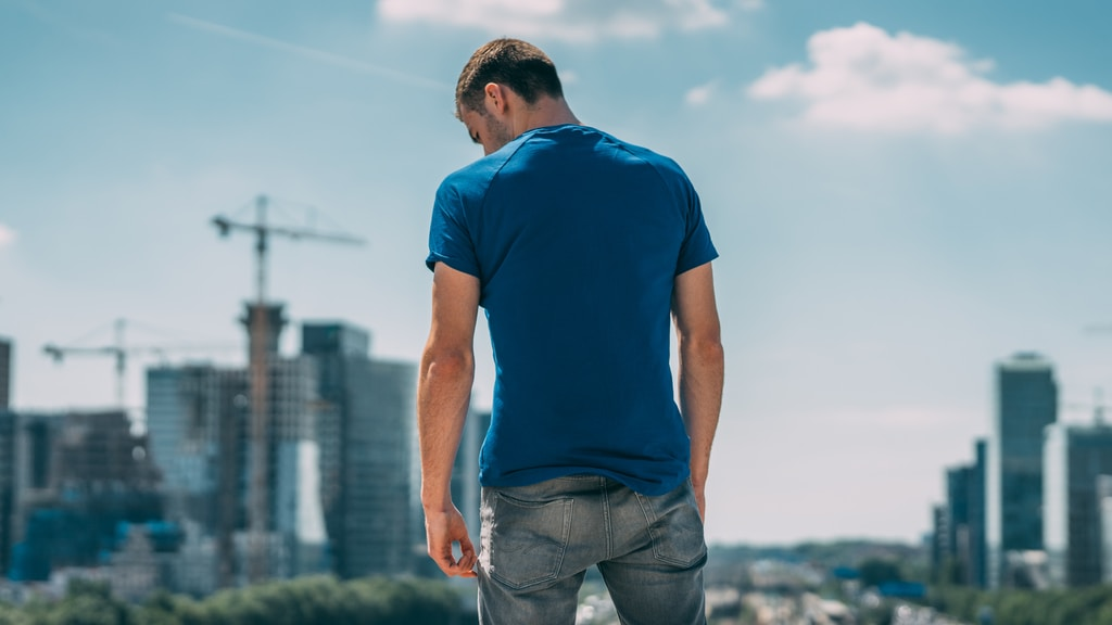 man in blue crew neck t-shirt and gray denim jeans standing on green grass field