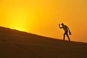 silhouette of man walking on desert during sunset