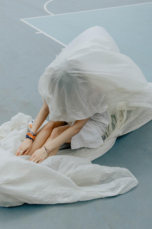 woman in white dress lying on white textile