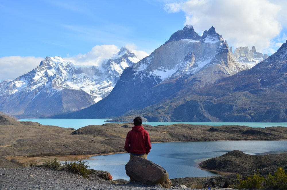 man in red hoodie sitting on rock near lake and snow covered mountain during daytime