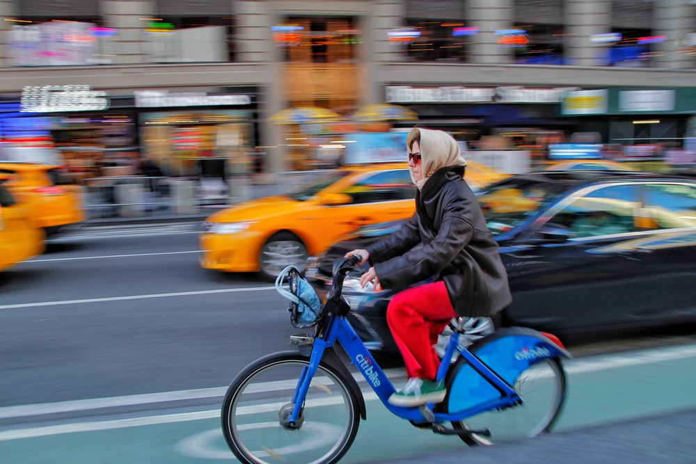 woman in black jacket riding blue motorcycle on road during daytime