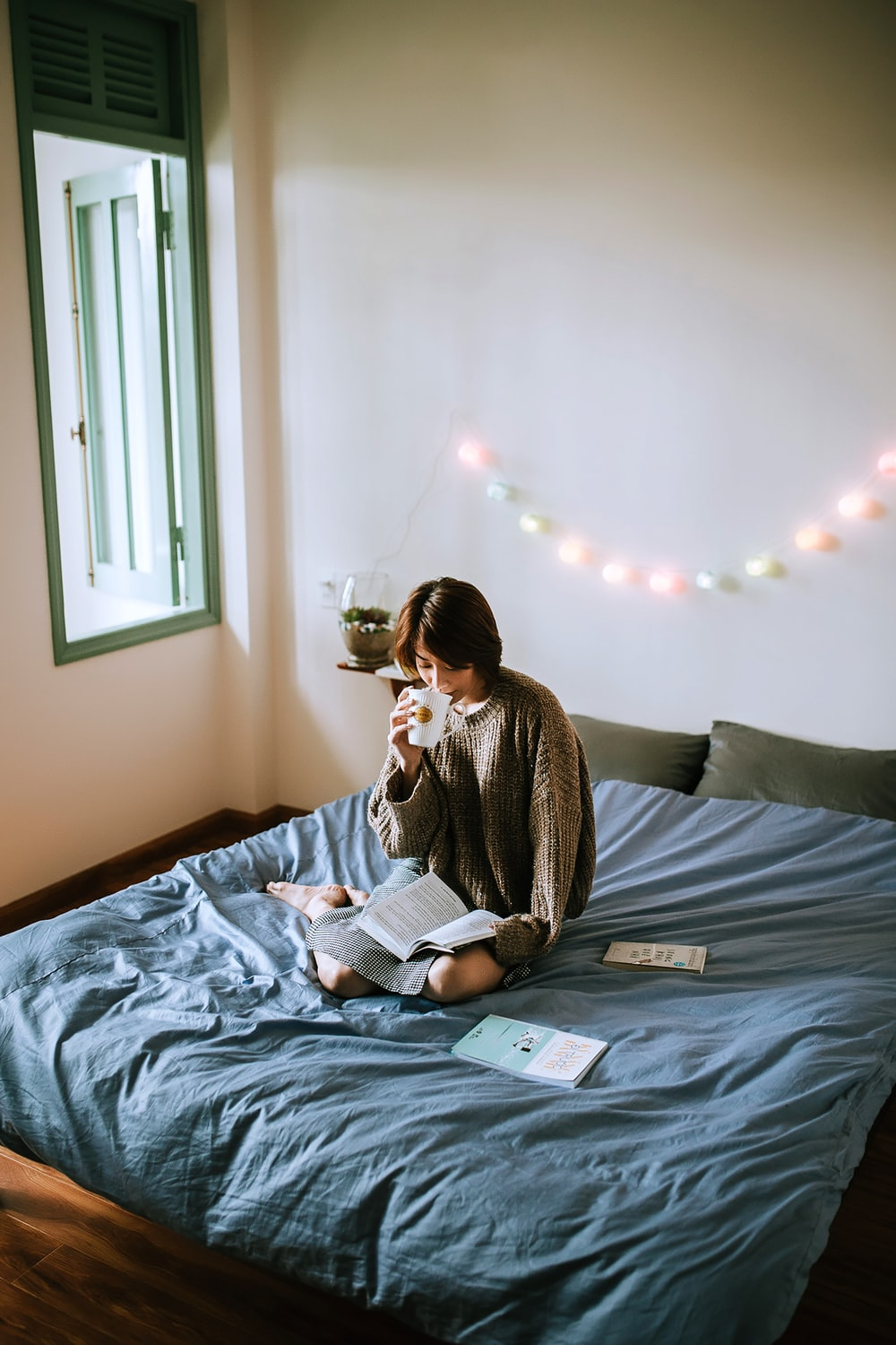 woman in gray sweater sitting on bed